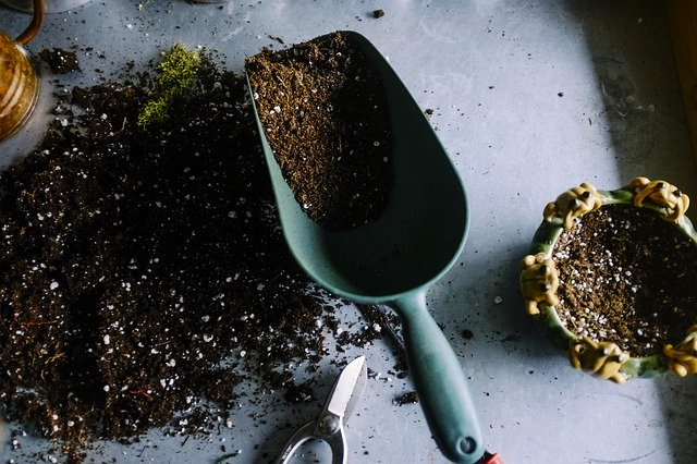 garden trowel filled and surrounded by dirt